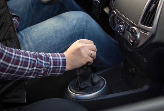 Closeup tiro de jovem trocando a caixa de marchas manual no carro