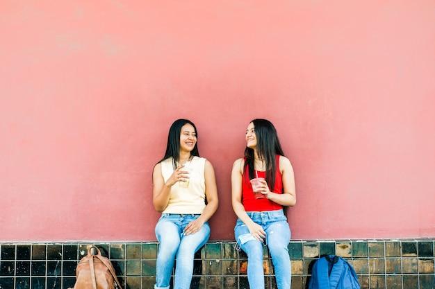 Closeup tiro de jovens alegres sentadas bebendo smoothies
