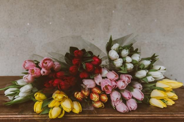 Closeup tiro de lindos buquês de tulipas coloridas em cima da mesa