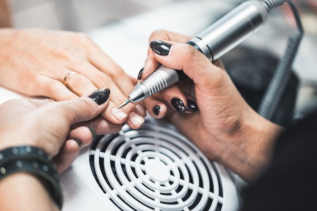 Closeup tiro de manicure de hardware em um salão de beleza. manicure está aplicando broca de lima de unha elétrica para manicure em dedos femininos.