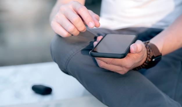 Closeup tiro de mãos de homem segurando um smartphone de tela em branco enquanto está sentado ao ar livre, profundidade de campo rasa.