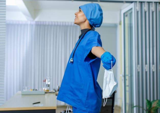 Closeup tiro de máscara cirúrgica usada na mão da médica feliz e sorridente da liberdade feminina em luvas de borracha de uniforme de hospital azul e estetoscópio no fundo desfocado após o fim da pandemia de coronavírus.