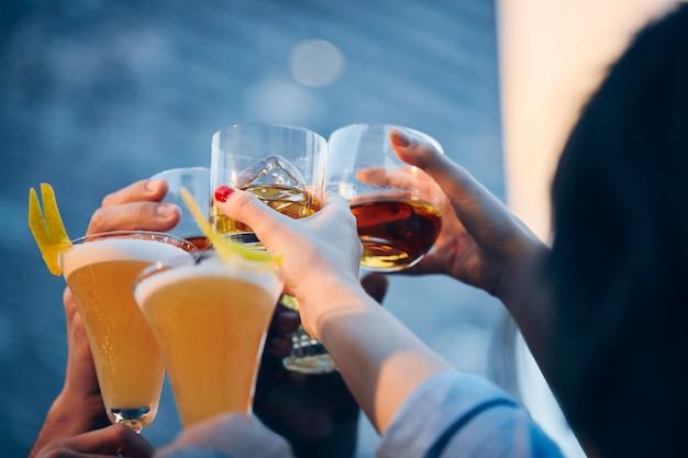 Closeup tiro de muitas pessoas a tilintar copos com álcool para um brinde
