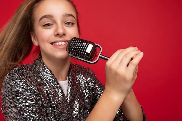 Closeup tiro de muito feliz positivo menina morena com vestido elegante brilho em pé isolado sobre a parede de fundo vermelho cantando a música para o microfone de prata, olhando para a câmera.