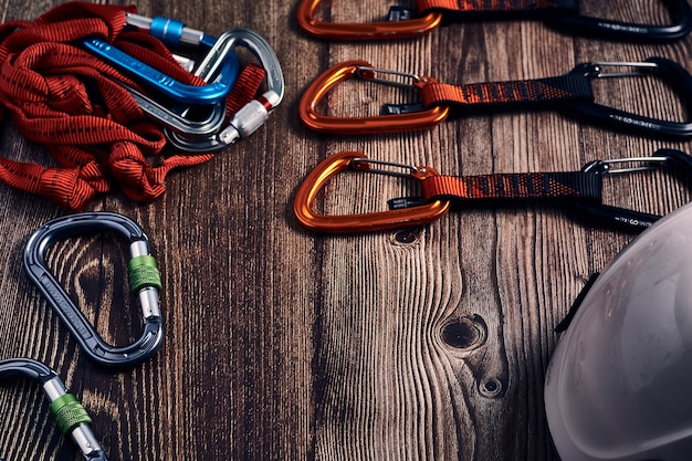 Closeup tiro de muitos mosquetões de escalada coloridos e nós em uma superfície de madeira