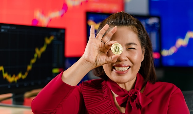 Closeup tiro de ouro bitcoin eletrônico criptomoeda dinheiro na mão do investidor empresária no fundo desfocado com computador monitor gráfico gráfico negociação compra venda tela mercado financeiro.
