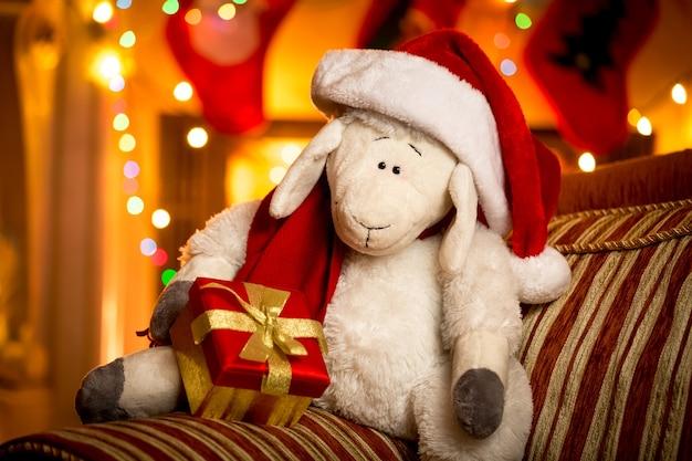Closeup tiro de ovelha de brinquedo com caixa de presente decorada para sala de estar de natal