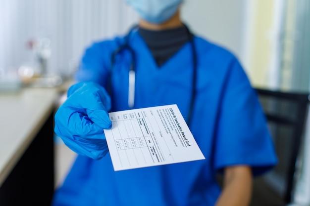 Closeup tiro de papel de passaporte certificado de cartão de registro de vacinação covid-19 enviado ao paciente pelo médico usa luvas de borracha de máscara facial de uniforme hospitalar azul e estetoscópio no fundo desfocado.