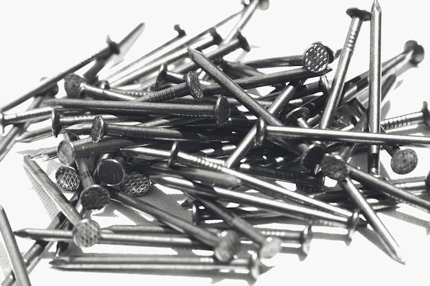 Closeup tiro de pregos de metal em uma superfície branca