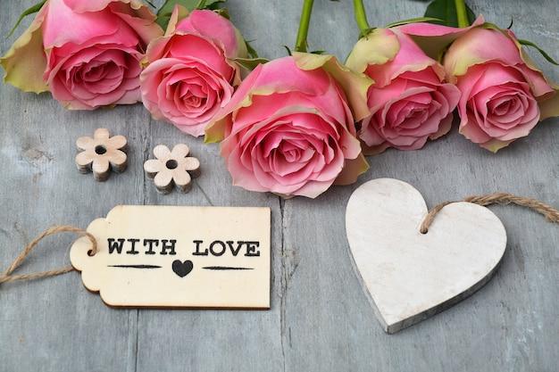 Closeup tiro de rosas cor de rosa ao lado de uma etiqueta de madeira de coração vazio e uma etiqueta com amor em uma superfície de madeira