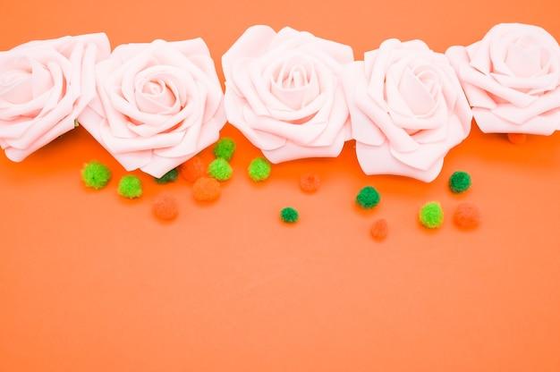 Closeup tiro de rosas cor de rosa e pompons coloridos isolados em fundo laranja