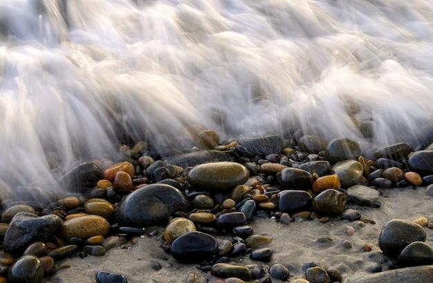 Closeup tiro de seixos cobertos com espuma do mar