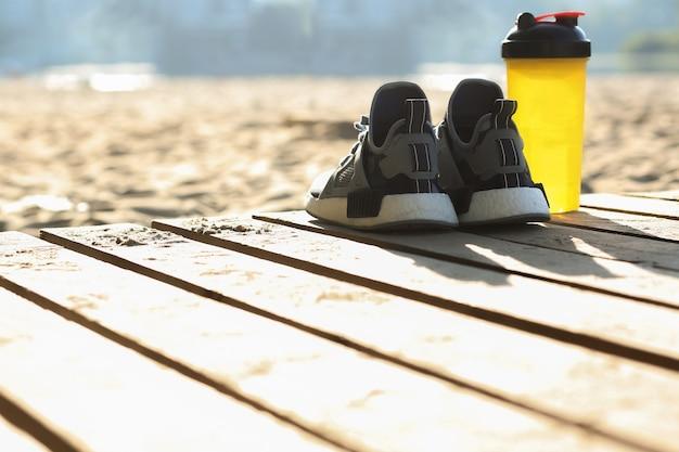 Closeup tiro de tênis de mulher e a garrafa de água em pé na praia. espaço vazio