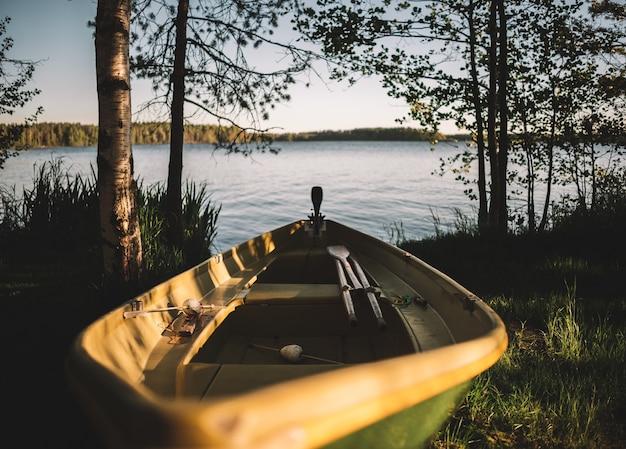 Closeup tiro de um barco de pesca na grama verde perto do lago ao nascer do sol