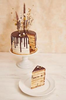 Closeup tiro de um bolo de baunilha com gotas de chocolate e flores no topo
