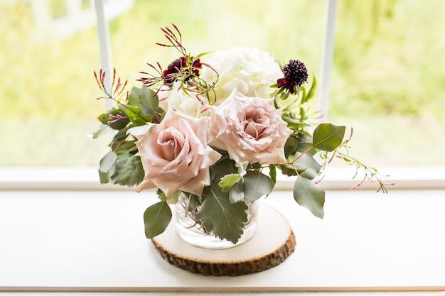 Closeup tiro de um buquê com rosas em um vaso perto de uma janela sob a luz do sol