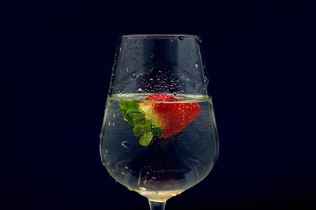 Closeup tiro de um copo de coquetel de vinho frio com um morango em um escuro