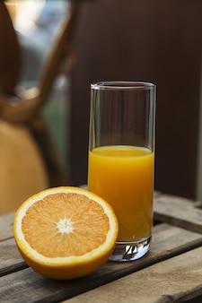 Closeup tiro de um copo meio cheio de suco de laranja e uma laranja em fatias em uma caixa de madeira