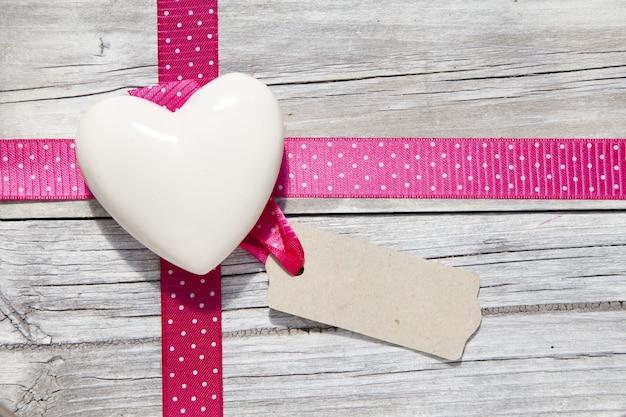Closeup tiro de um coração branco com um laço em uma superfície de madeira com um espaço de cópia