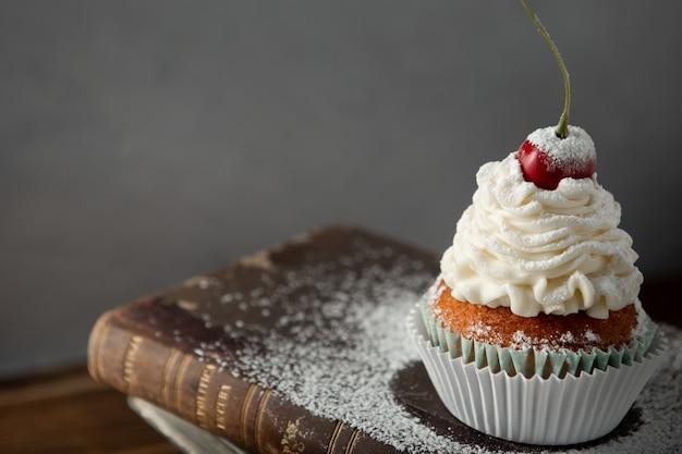 Closeup tiro de um delicioso bolinho com creme, açúcar de confeiteiro e uma cereja em cima do livro