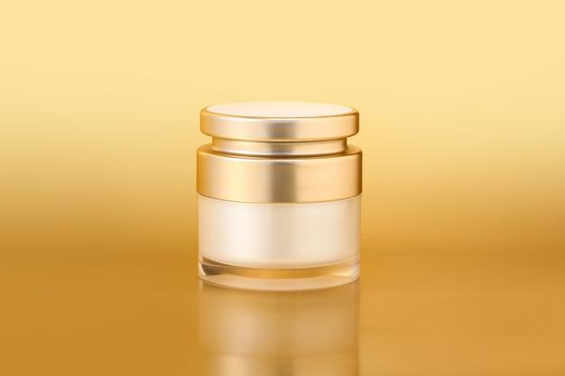 Closeup tiro de um elegante contêiner de ouro para cuidados com a pele em um fundo dourado
