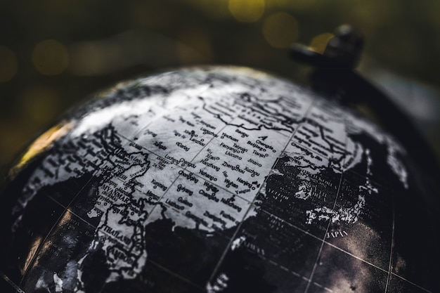 Closeup tiro de um globo de madeira preto e branco com um fundo desfocado