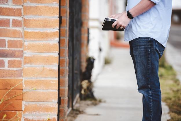 Closeup tiro de um homem em pé perto de um edifício, mantendo a bíblia