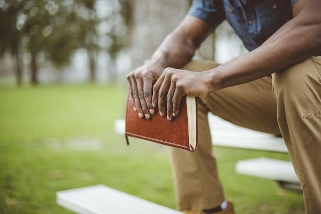 Closeup tiro de um homem segurando a bíblia enquanto está sentado em uma mesa do parque