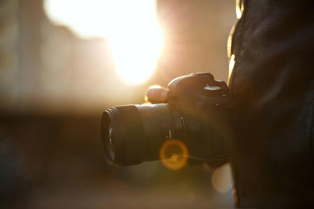 Closeup tiro de um homem segurando a câmera digital contra a luz do sol. espaço para texto