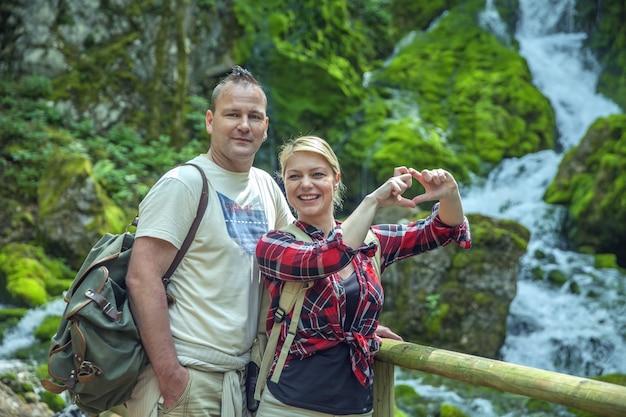 Closeup tiro de um lindo casal apaixonado na natureza com uma cachoeira à distância