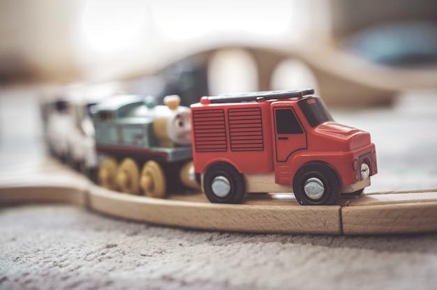 Closeup tiro de um pequeno carrinho de brinquedo na linha de um trem de madeira