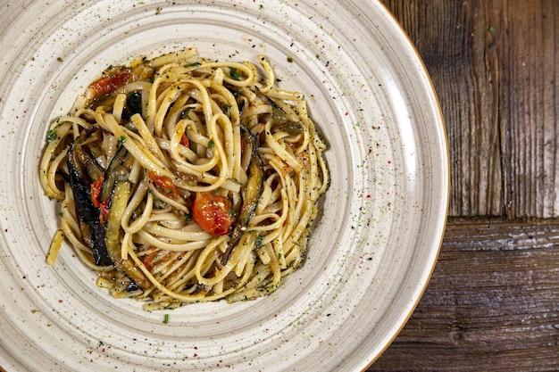 Closeup tiro de um prato branco cheio de espaguete e vegetais em uma superfície de madeira
