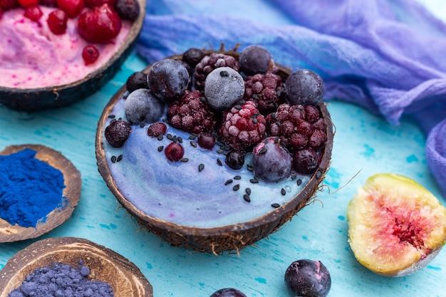 Closeup tiro de um shake de frutas coberto com framboesas congeladas e mirtilos em uma tigela de coco