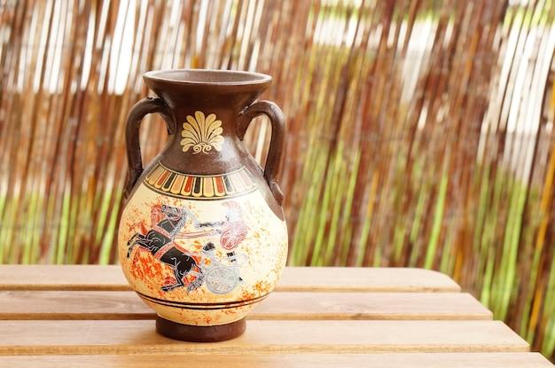 Closeup tiro de um vaso grego em uma mesa de madeira