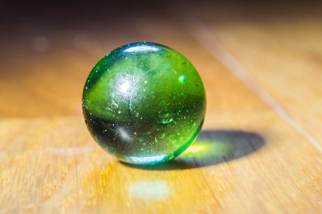 Closeup tiro de uma bola de gude verde em cima de uma mesa de madeira