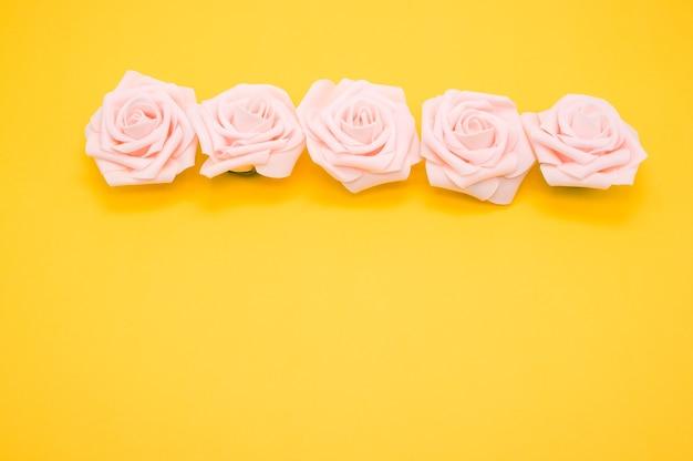 Closeup tiro de uma fileira de rosas cor de rosa isoladas em um fundo amarelo com espaço de cópia