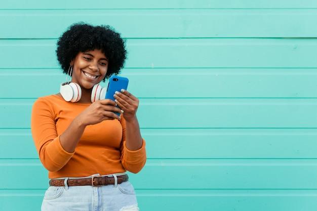 Closeup tiro de uma jovem atraente usando fones de ouvido e usando o telefone