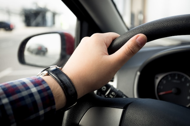 Closeup tiro de uma mão masculina em relógios segurando o volante de um carro
