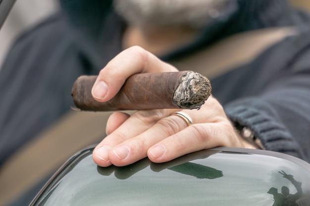 Closeup tiro de uma mão masculina segurando um charuto