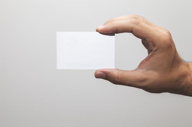 Closeup tiro de uma mão segurando um papel em branco