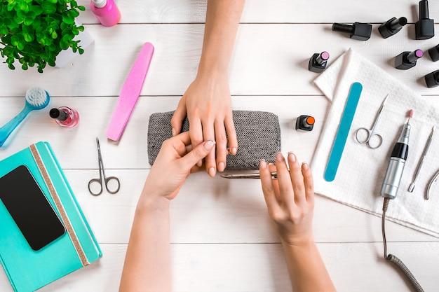 Closeup tiro de uma mulher em um salão de beleza recebendo uma manicure por uma esteticista com lixa de unha. mulher recebendo unhas manicure. lixa as unhas da esteticista para uma cliente.