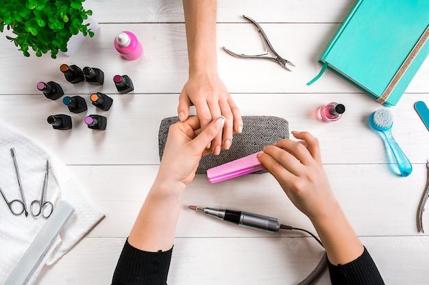 Closeup tiro de uma mulher em um salão de beleza recebendo uma manicure por uma esteticista com lixa de unha. mulher recebendo unhas manicure.