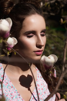Closeup tiro de uma mulher morena sensual em pé perto de flores desabrochando de magnólia