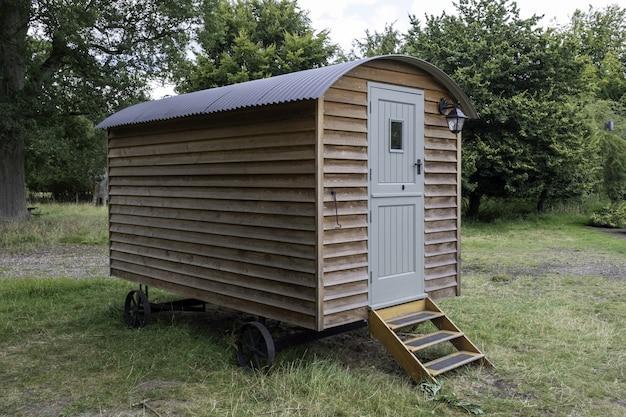 Closeup tiro de uma pequena casa de madeira sobre rodas