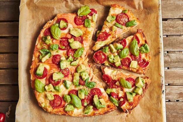 Closeup tiro de uma pizza com legumes na mesa de madeira