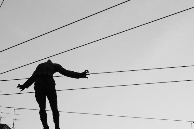 Closeup tiro de uma silhueta de uma pessoa no ar com cabos indo atrás do corpo