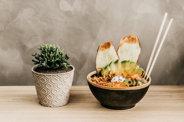 Closeup tiro de uma tigela cheia de comida e um vaso de plantas em uma mesa de madeira
