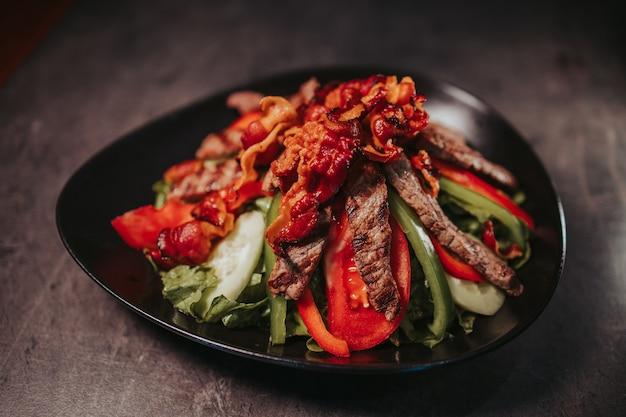 Closeup tiro de uma tigela de prato de carne deliciosa em uma mesa de madeira