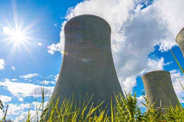 Closeup tiro de uma torre de resfriamento de uma usina nuclear atrás da grama verde em um lindo dia de sol