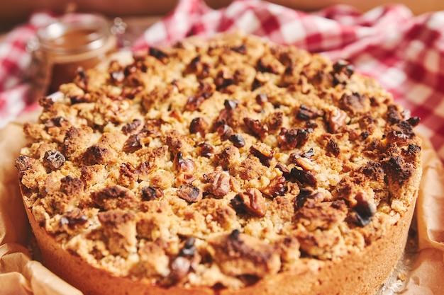 Closeup tiro de uma torta de maçã redonda coberta com crumble e nozes torradas, em uma toalha